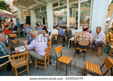 IZMIR PROVINCE, TURKEY - JUL 28: Senior men sitting around tables and talking in rustic cafe of old village on July 28, 2015. Population of Izmir province is 3.950.000 people - stock photo
