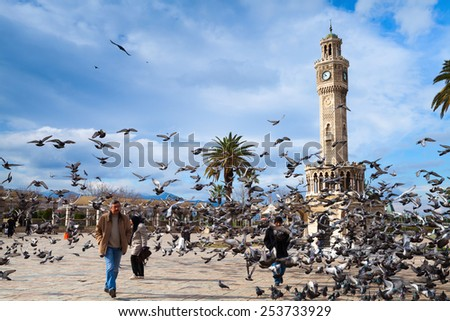 Izmir, Turkey - February 12, 2015: Doves flying near the historical clock tower, it was built in 1901 and accepted as the symbol of Izmir City. Konak Square  - stock photo