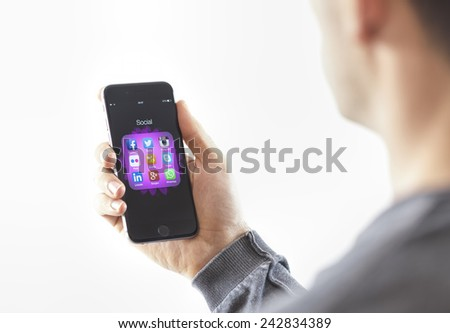 Izmir, Turkey - January 3, 2015: Man trying his new iPhone 6 Space Gray in his hand. iPhone 6 was created and developed by the Apple inc. - stock photo
