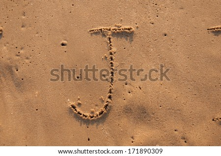 J text written in the sandy on the beach - stock photo