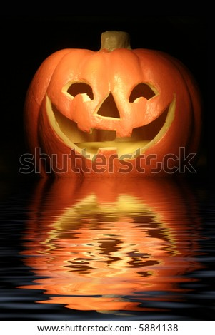 jack-o-lantern against a dark background with reflection - stock photo