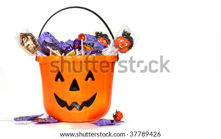 Jack-o-Lantern bucket filled with candies on white background - stock photo