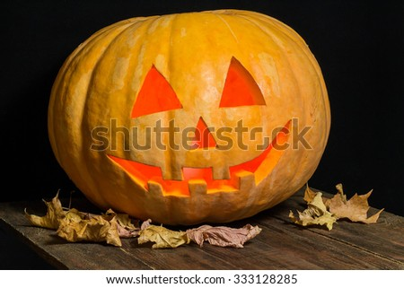 Jack-o-lantern from a huge pumpkin and dry leaves on a wooden table - stock photo