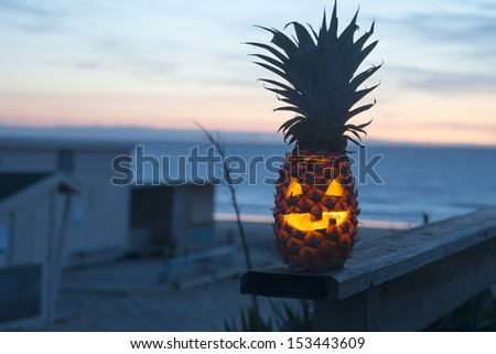 Jack o lantern halloween face carved into pineapple instead of pumpkin. Tropical fruit with ocean in background - stock photo