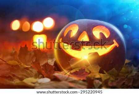 Jack O Lantern halloween pumpkin in leaves - stock photo