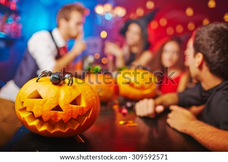 Jack-o-lantern on bar counter and friends on background - stock photo