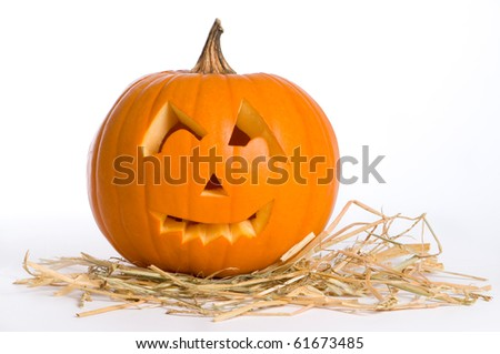 Jack O Lantern with carved face sitting on a bed of straw - stock photo