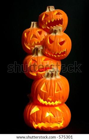 Jack O Lanterns - a stack of pumpkins carved into lighted jack-o-lanterns over black background for Halloween. - stock photo