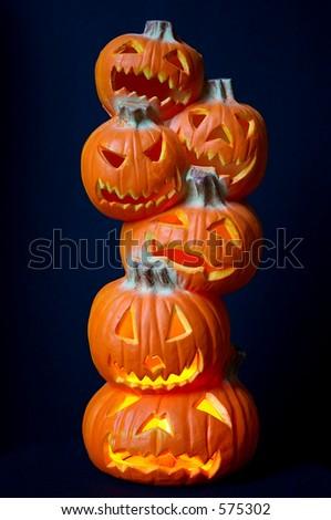 Jack O Lanterns - a stack of pumpkins carved into lighted jack-o-lanterns over deep blue background for Halloween. - stock photo