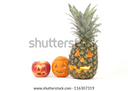 Jack-o-lanterns made from pineapple, apple and orange creating tropical halloween decoration - stock photo