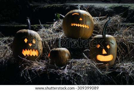 Jack O lanterns pumpkins on straw - halloween night - stock photo