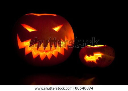 Jack-o'-lanterns, spooky Halloween pumpkins glowing in the night. - stock photo