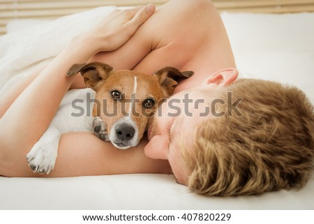 jack russell dog  in bed sleeping with owner close together and cuddling