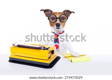 jack russell secretary dog typing on a typewriter keyboard  a note pad and pencil beside, isolated on white background - stock photo