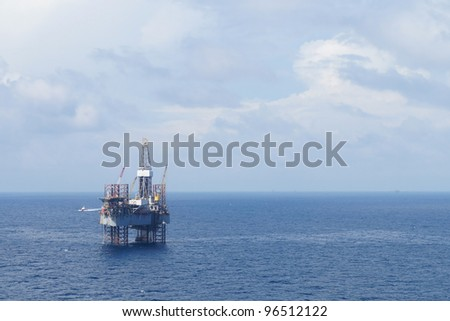 Jack up drilling rig and crew boat in the middle of the coean - stock photo