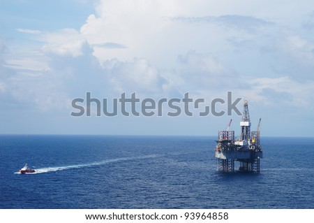 Jack up drilling rig and crew boat in the middle of the ocean - stock photo