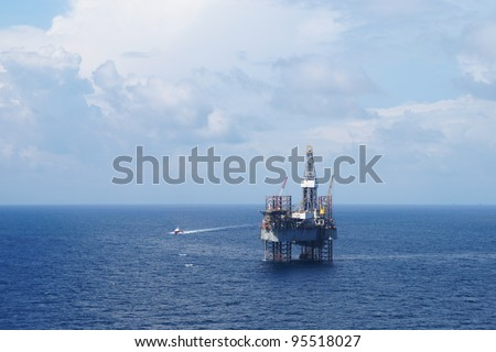 Jack up drilling rig and crew boat on sunny day - stock photo