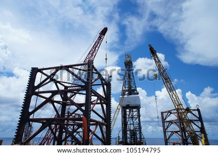 Jack Up Offshore Drilling Rig With Rig Cranes in The Middle of Ocean - stock photo