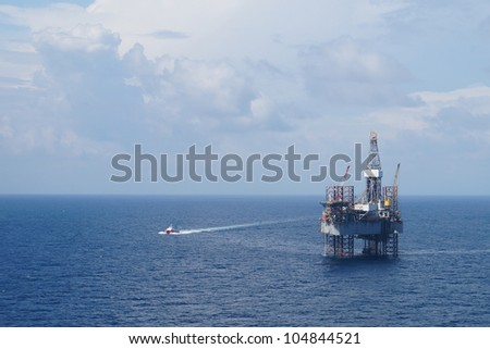 Jack up oil drilling rig and a crew boat - stock photo