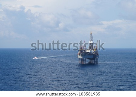 Jack up oil drilling rig and a crew boat in the middle of the ocean - stock photo