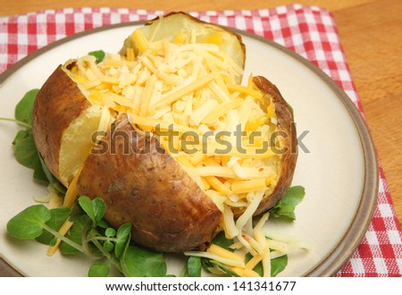 Jacket potato with shredded cheeses.
