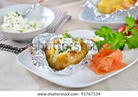 Jacket potato with sour cream and smoked salmon - stock photo