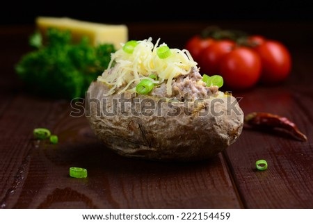 Jacket potato with tuna and cheese garnished with green onion on dark brown wooden table. Low key photography - stock photo