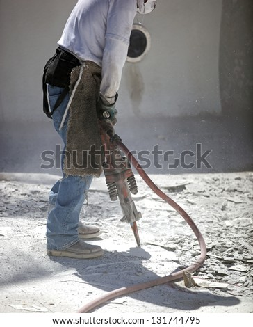 Jackhammer breaking up swimming pool for resurfacing - stock photo
