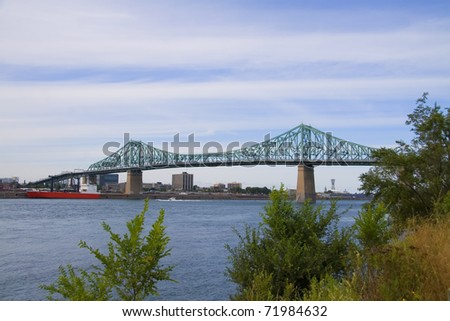 Jacques Cartier bridge spanning over the Saint Lawrence river - stock photo