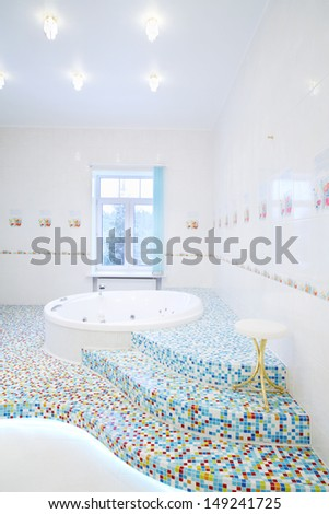 Jacuzzi and stairs in spacious white bathroom with tiles with poppies. - stock photo