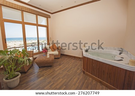 Jacuzzi in private room of luxury health spa with chairs and sea view - stock photo