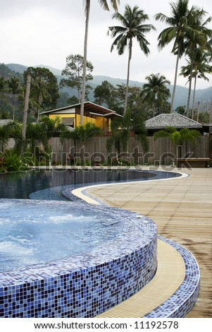 Jacuzzi in the foreground on a picture of a health resort. Leisure and relaxation concept. - stock photo