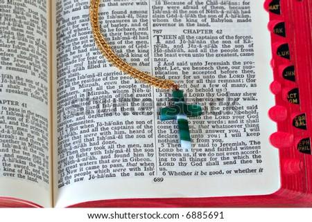 Jade Cross on Open Bible, Shallow DOF - stock photo