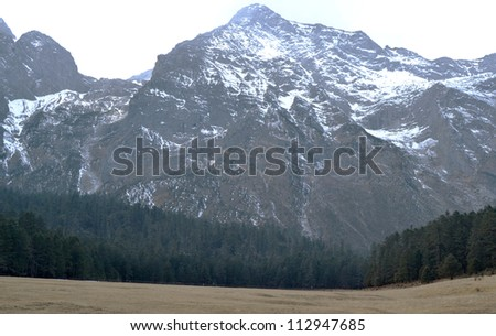 Jade Dragon Snow Mountain or Mount Yulong mountain and forest nature view in western china desolation background in Lijiang country, Yunnan province - stock photo