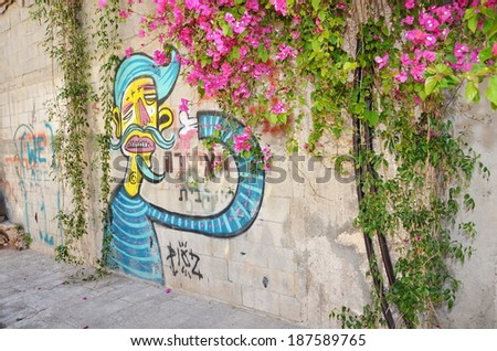 JAFFA, ISRAEL - APR 11, 2014: Graffiti in the shape of a blue-haired man on a wall in Jaffa, Tel Aviv, Israel - stock photo