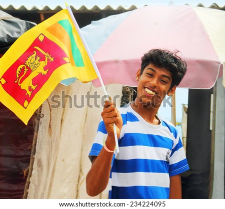 JAFFNA/SRI LANKA - AUG 12: Unidentified boy poses for a photo with a national flag on August 12, 2013 in Jaffna, Sri Lanka, South Asia. Symbols on the flag manifests the main religions of the country. - stock photo