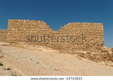 Jagged wall of ancient fortress ruin in the desert near the Dead Sea - stock photo