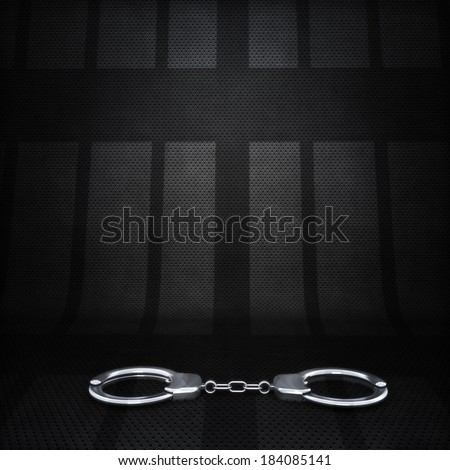 Jail scene background. Hand cuffs with silhouette of cell doors in the background - stock photo