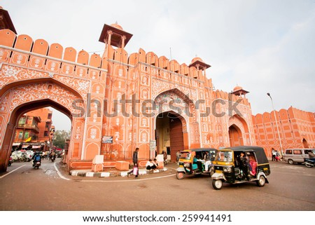 JAIPUR, INDIA - JAN 24: Auto rickshaw drive fast near the old Ajmer gate of historical Pink City wall on January 24, 2015. Jaipur, with population 6,664,000 people, is a capital of Rajasthan - stock photo