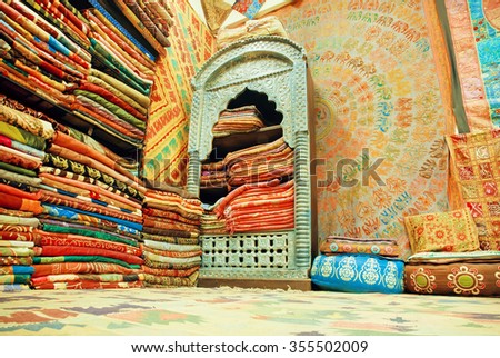JAIPUR, INDIA - JAN 22: Cupboard of traditional Indian souvenir shop, full of silk shawls and scarves with different colors on January 22 2015. Jaipur with population 6,664000, is capital of Rajasthan - stock photo