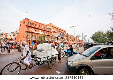 JAIPUR, INDIA - JAN 22: Traffic on the asian street full of cars, rickshaws and pedestrians of Pink City on January 22, 2015. Jaipur, with population 6,664000 people, is a capital of Rajasthan - stock photo
