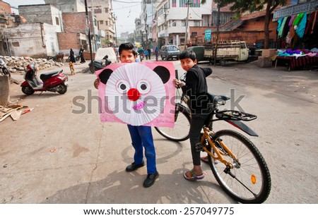 JAIPUR, INDIA - JAN 25: Unidentified children show off their artistic paper cut outs while walking on January 25, 2015. Jaipur, with population 6,664000 people, is a capital of Rajasthan - stock photo