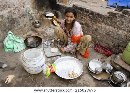 JAIPUR, INDIA - MARCH 02: Unidentified indian poor girl cooking chapatti on March 02, 2013 in Jaipur, India. Chapati - a traditional Indian flatbread - stock photo