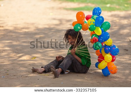 JAIPUR,INDIA - March 30, 2013 : Unidentified poor child tries to sell balloons and eats food that she can find in the streets of the city. - stock photo