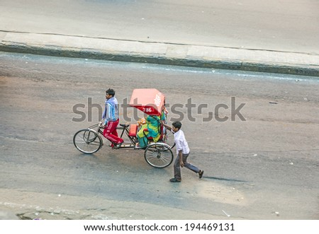 JAIPUR, INDIA - NOV 13, 2011: Rickshaw rider transports women in Jaipur, India.ycle rickshaws were introduced in Jaipur in the 1940's and have a fixed quota of licenses. - stock photo