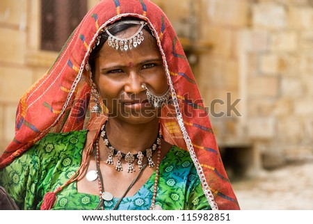 JAISALMER, INDIA - 14 AUGUST: unidentified woman pose for tourists in a traditional dress in Jaisalmer, 14 august 2008. Many women stay in front of the walls of Jaisalmer selling jewels and posing. - stock photo