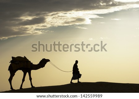 JAISALMER, INDIA-FEB 26: A desert local walks a camel through Thar Desert, on Feb 26, 2013 in Jaisalmer, India. Apart from farming, camel riding activity is another income source for desert villagers - stock photo