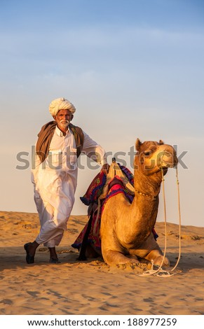 JAISALMER, INDIA - FEB 26: Cameleer and his herd at the Sam Sand Dune on  Feb 26, 2013 in Jaisalmer, India. Apart from farming, camel riding activity is  another income source for desert villagers - stock photo