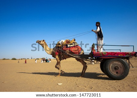 JAISALMER, INDIA - FEB 25:  Cameleer at the Sam Sand Dune on Feb 25, 2013 in Jaisalmer, India.  Apart from farming, camel riding activity for tourists is another income source for desert villagers