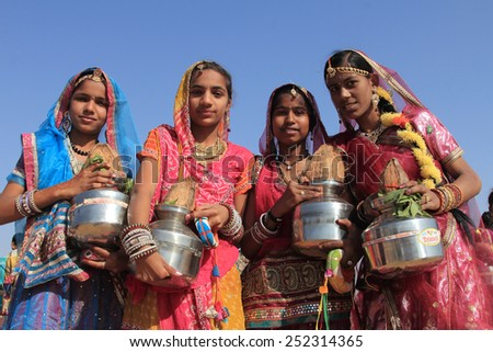 JAISALMER, INDIA - FEB 01: Traditionally dressed Rajasthani dancers holding pots perform during a cultural procession for Desert festival held on February 01, 2015 in Jaisalmer, Rajasthan,India. - stock photo